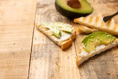 Toast with philadelphia cheese, avocado pieces and sesame seeds on wooden background, healthy and healthy food , vegan food, detox royalty free stock photo