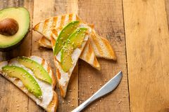 Toast with philadelphia cheese, avocado pieces and sesame seeds on wooden background, healthy and healthy food , vegan food, detox stock images