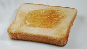 Toast on a plate pour with honey. 4K UHD 3840x2160 Video Clip stock photos