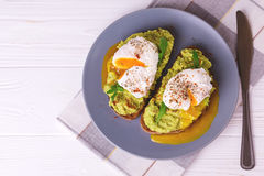 Toast with poached egg, puree avocado, spices and arugula. Rye bread toast with poached egg, puree avocado, spices and arugula. Continental breakfast. Healthy royalty free stock photography