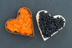 Toast with red and black caviar in the form of heart on dark Stock Image