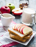 Toast with ricotta and sweet red apple, a cup of milk Stock Image