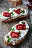 Toast of rye bread with different seeds with ricotta cheese, sun-dried tomatoes, capers, parsley and olive oil. Stock Photos