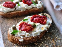 Toast of rye bread with different seeds with ricotta cheese, sun-dried tomatoes, capers, parsley and olive oil. Stock Photo