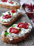 Toast of rye bread with different seeds with ricotta cheese, sun-dried tomatoes, capers, parsley and olive oil. Stock Images