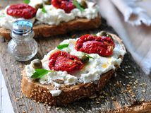 Toast of rye bread with different seeds with ricotta cheese, sun-dried tomatoes, capers, parsley and olive oil. Royalty Free Stock Photography