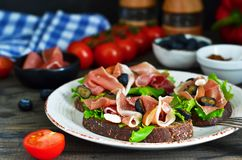 Toast of rye bread with jamon, blueberries and almonds. royalty free stock photo