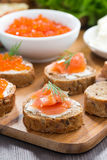 toast with salted salmon and red caviar on wooden board Stock Photography