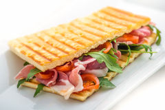 Toast sandwich with ham, tomatoes and arugula salad on white plate Stock Photos