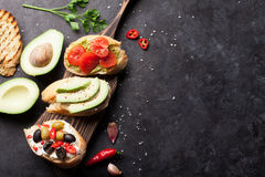 Toast sandwiches. With avocado, tomatoes and olives on stone background. Top view with copy space stock photography