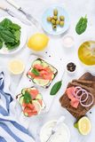 Toast sandwiches with salmon, cream cheese, olives and cucumber on white table. Top view. Dinner table royalty free stock photo