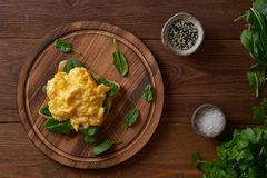 Toast with scrambled eggs and spinach. Omelette. Breakfast with pan-fried eggs on brown dark background. Top view stock images