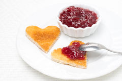 Toast in the shape of hearts and berry jam on the plate Royalty Free Stock Images