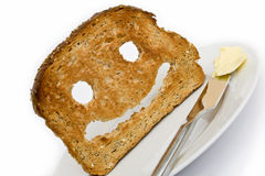 Toast smile. Smiley made from toasted bread with knife plate and butter royalty free stock photography