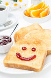 Toast with a smile of jam, coffee, fresh oranges for breakfast Royalty Free Stock Photography
