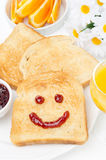 Toast with a smile of jam, coffee, orange juice and fresh orange Stock Image