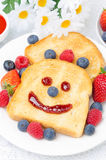 Toast with a smile out of a jam, fresh berries for breakfast Royalty Free Stock Images
