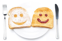 Toast with smile of powdered sugar and jam on plate, fork, knife Stock Photos