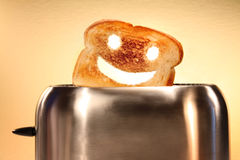 Toast with smiley face in toaster Stock Photos