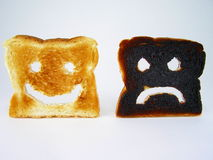 Toast Smiley and Frowney. Breakfast toast, one very happy and the other one not so happy. Might be due to the burn Stock Image