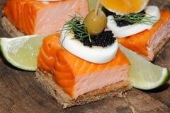 Toast, smoked salmon, egg, caviar, orange, grape, olive Stock Photo