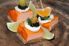 Toast, smoked salmon, egg, caviar, orange, grape, olive Royalty Free Stock Photo