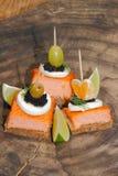 Toast, smoked salmon, egg, caviar, orange, grape, olive Stock Photos