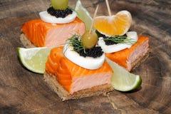 Toast, smoked salmon, egg, caviar, orange, grape, olive Royalty Free Stock Image
