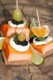 Toast, smoked salmon, egg, caviar, orange, grape, olive Royalty Free Stock Images