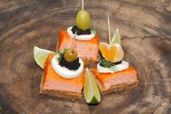 Toast, smoked salmon, egg, caviar, orange, grape, olive Stock Image