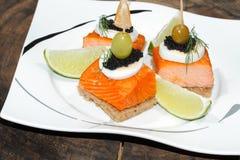 Toast, smoked salmon, egg, caviar, orange, olive, grape Stock Photos