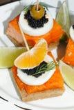 Toast, smoked salmon, egg, caviar, orange, olive, grape Royalty Free Stock Photos