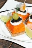 Toast, smoked salmon, egg, caviar, orange, olive, grape Royalty Free Stock Image