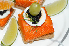 Toast, smoked salmon, egg, caviar, orange, olive, grape Royalty Free Stock Photography