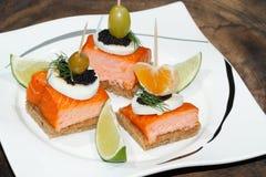 Toast, smoked salmon, egg, caviar, orange, olive, grape Stock Image