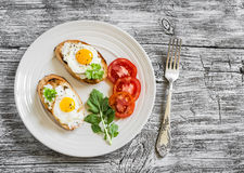 Toast with soft cheese and quail eggs on a white plate Stock Image