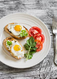 Toast with soft cheese and quail eggs on a white plate Royalty Free Stock Photography