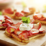Toast with strawberries mascarpone and lemon and a garnish. Of mint royalty free stock photography