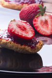 Toast with strawberry jam on black background plate Stock Photos