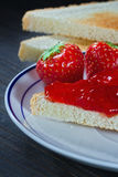 Toast with strawberry jelly on black background Stock Photos