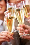 Toast for success. Image of businesspeople hands holding crystal glasses full of champagne Royalty Free Stock Photo
