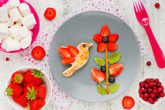 Toast with sugar and berry fruit in the form of a hummingbird on Stock Photography