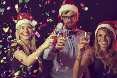 Toast. Three young people on a New Years eve party giving a toast on midnight Stock Images