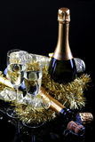 Toast to the beginning of the year. Glasses of sparkling wine with bottles on a black background with decorations Stock Photography