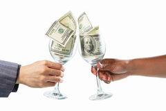 Toast using glass filled with dollar bills Royalty Free Stock Photo