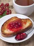 Toast of white bread with red currant jam, spoon with jam Stock Photo