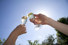Toast in white wine. Two hands touch glasses making a toast against a blue sky Royalty Free Stock Photos