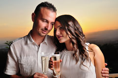 Toast young couple dressed in white at sunset Royalty Free Stock Image