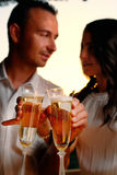 Toast young couple with glasses in the foreground at sunset Royalty Free Stock Photography