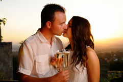 Toast young couple kissing at sunset Stock Photos